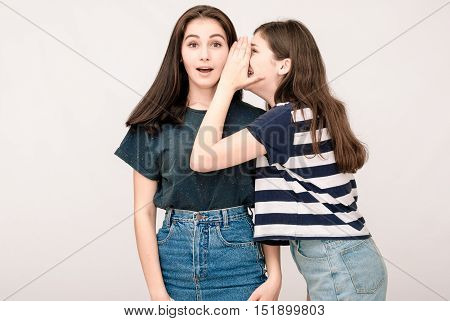 Portrait of a two girls gossip on gray background. Funny faces, grimaces, joy, emotions, casual style