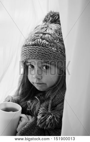 Black-and-white Photo Of A Cute Little Girl In Fashionable Winter Clothes