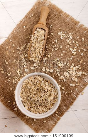 organic scottish toasted oats in a bowl wooden scoop and brown jute