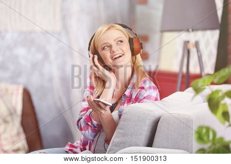 Cheerful girl with headphones and phone listening to music at home