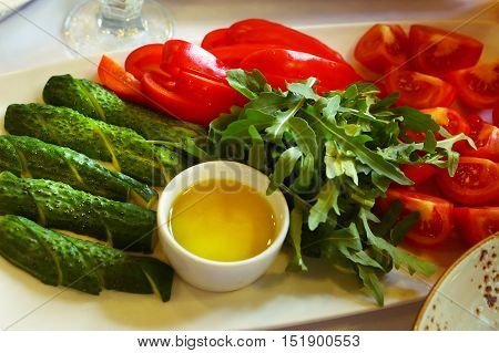 cut cucumbers and tomatoes pepper parsley with oil sauce close up photo