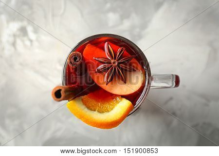 Glass cup of delicious Christmas mulled wine on gray background, closeup