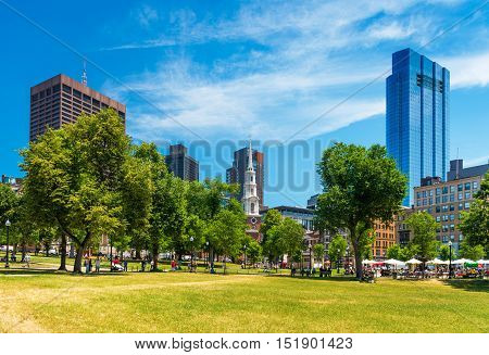 Boston, MA - July 2016, USA: People sitting on grass and walking around in Boston Common Park, view on Skyscrapers and Park street Church