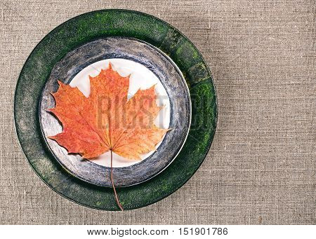 Flat lay of plates with fallen leaves on linen tablecloth