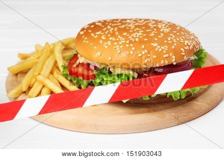 Tasty hamburger and french fries crossed with warning tape. Diet concept