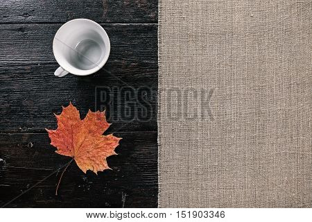 still life with empty tea cup and fallen maple leaf. Flat lay
