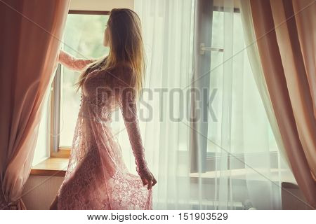 Near the window is a woman in a transparent peignoir.