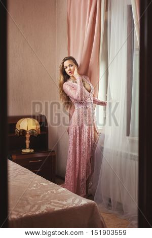 Woman in a transparent peignoir bedroom window.