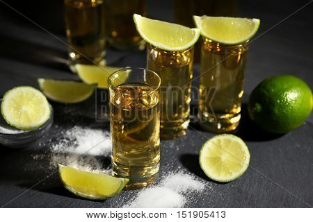 Gold tequila shots with lime and salt on gray background