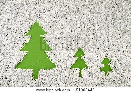 three green fir symbols made inside big heap of shredded paper