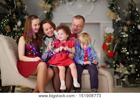 Mother, father, son and two daughters pose with luminous garland during christmas
