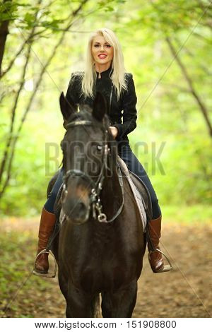 Blonde young woman in black rides horse in green autumn park