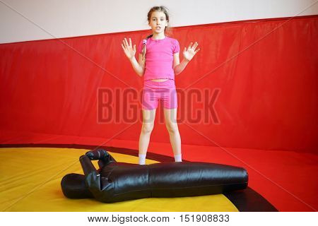 Girl in pink prepares for fighting exercises with leather mannequin in gym