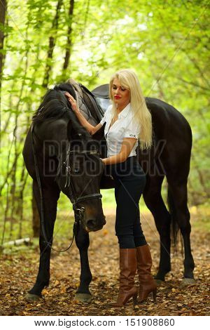 Blonde beautiful woman and black horse in green sunny autumn park