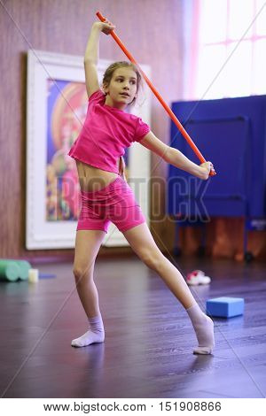 Girl in pink dances with red sport stick in gym hall, shallow dof