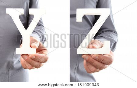 Hands holding letter Y and Z from alphabet isolated on a white background