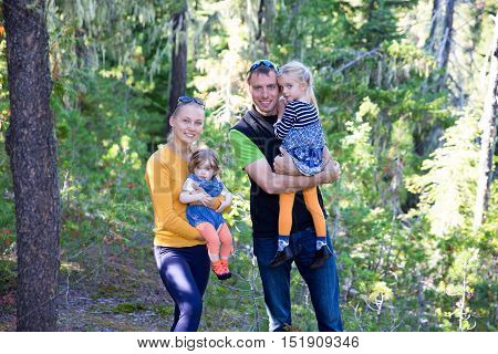 Happy family concept young active parents with their two little girls in the Forest.