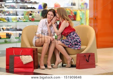 Two beautiful girls sit in shop and whisper and gossip in big modern shop