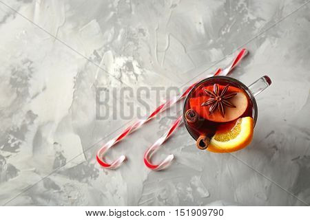 Glass cup of delicious Christmas mulled wine on gray background