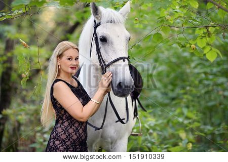 Woman in long black dress poses near beautiful white horse in park, focus on horse
