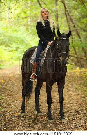 Blonde young woman in black sits on horse in green autumn park