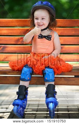 Girl in roller skates sits on bench and thumps up at summer day