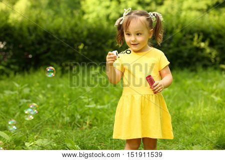 Cute little girl in yellow blows soap bubbles in green summer park