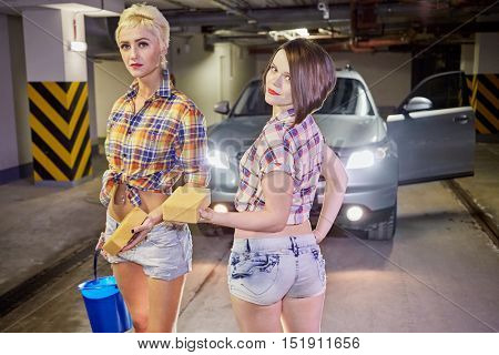 Two young girls in shorts and shirts pose in front of car with sponges and bucket with water at underground parking garage.