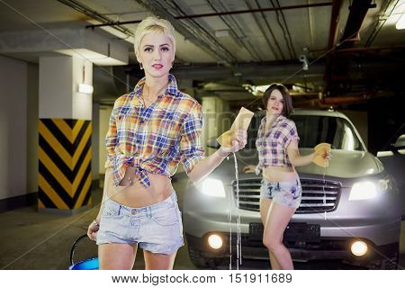 Two young girls in shorts and shirts pose in front of car with sponges and bucket with water at underground parking garage, focus on first girl.
