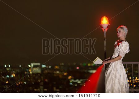 Young woman in white dress stands at roof fencing holding pile of letters in evening.
