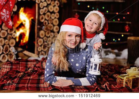 Mother and son in Christmas red caps lying on a plaid blanket on the background of a burning fireplace.