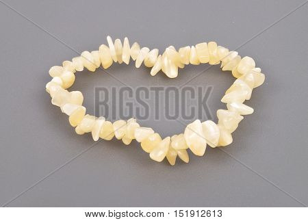 Colorful and crisp image of splintered orange calcite chain on gray background