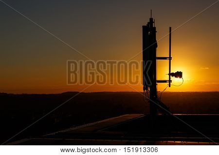 NOTTINGHAM ENGLAND - OCTOBER 5: Mobile communications mast/antenna atop a tall building against sunset. In Nottingham England. On 5th October 2016.