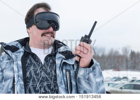 Smiling man in black ski goggles holds radio standing outdoor.