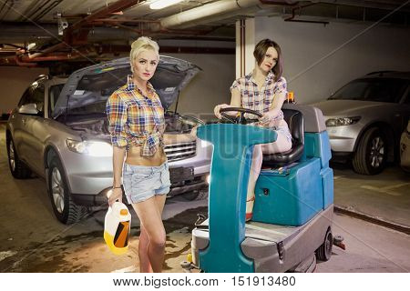 Two young women pose at floor scrubber machine in underground parking garage.