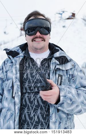 Half-length portrait of smiling man in black ski goggles holding radio standing outdoor.