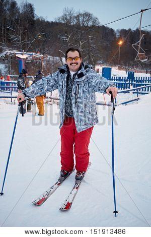 Smiling man poses standing on skis at ski resort.
