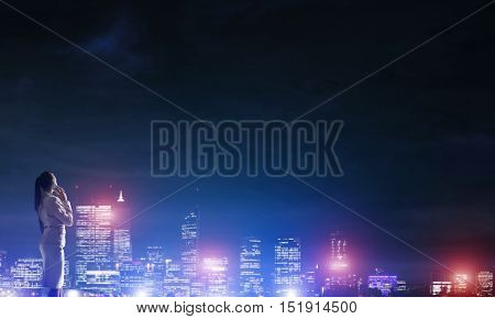 Rear view of elegant businesswoman talking mobile and viewing lights of night city