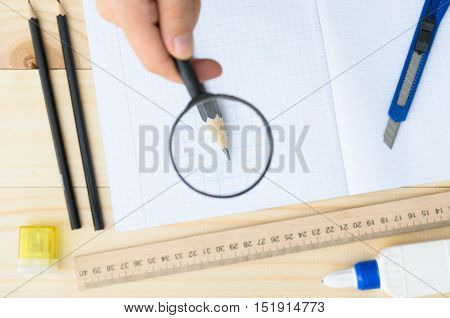 Workplace. School or office stationery on wooden board with copyspace. hand with magnifier