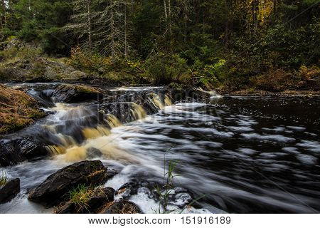 Michigan Upper Peninsula Waterfall Background. Tioga Falls is a scenic area located at a rest area on Highway 28 outside of Marquette, Michigan.