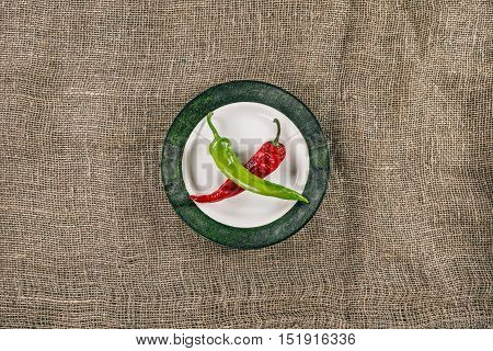 Plate with red and green hot peppers crossing as bones of pirate symbol
