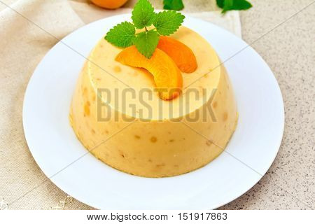 Dessert panna cotta cheesecake with apricots in a white plate, mint on a napkin on the background of a brown granite table