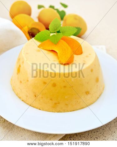 Dessert panna cotta cheesecake with apricots in a white plate, mint on a napkin, fruits on a background of brown granite table