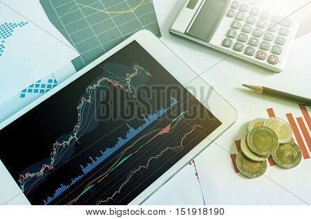 Business Concept. Modern Tablet With Stock Exchange Report Screen, Calculator, Coin And Pencil On Pa