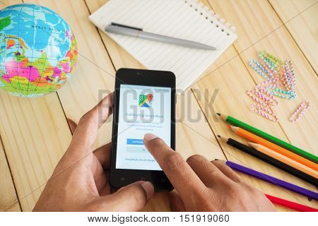 PHUKET, THAILAND AUG 19 2016 : Man hand holding smart phone mobile with Google Maps application Google Maps is a service that provides information about geographical regions and sites around