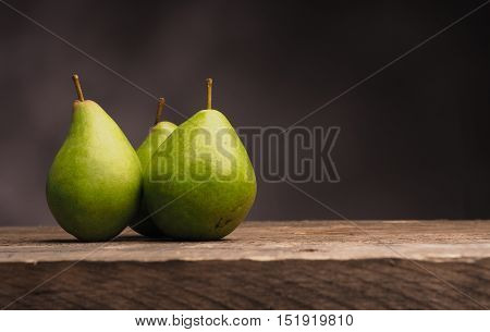 Three delicious green pears on an old wooden table with space for text