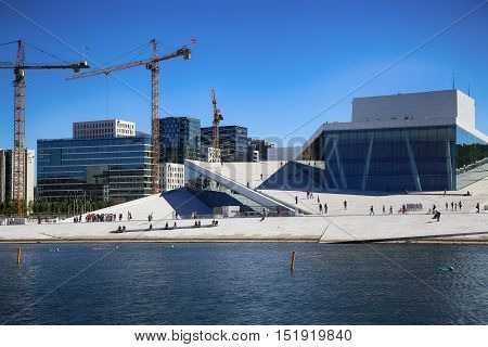 OSLO NORWAY - AUGUST 17 2016: Tourist on the Oslo Opera House which is home of Norwegian National Opera and Ballet and National Opera Theatre in Oslo Norway on August 172016.