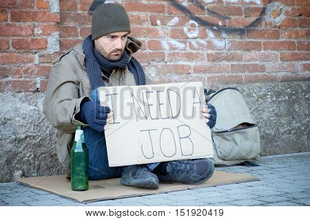Homeless Seated In The Street And Asking For A Job