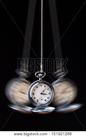 Swinging pocket watch hypnosis on a black background