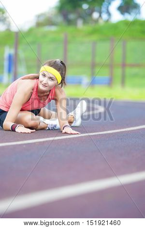 Female Sport Concepts. Young Caucasian Sporstwoman Having Stretching Exercises On Stadium Outdoors. Vertical Composition
